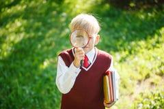 Portreta mały uczeń na natury tle Dziecko z książkami i loupe Edukacja dla dzieciaków tylna koncepcji do szkoły Fotografia Royalty Free