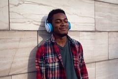 Portreta miastowy uśmiechnięty afrykański mężczyzna w bezprzewodowych hełmofonach cieszy się słuchać muzyka na szarość izoluje tł obraz royalty free