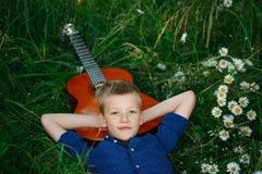 Portreta nastoletniego chłopaka lying on the beach na trawie z jego gitarą akustyczną zdjęcie stock