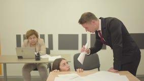 Portreta nerwowy młody człowiek składał papier i wrzeszczeć w postaci rogu przy kobiety obsiadaniem pod stołem w zbiory