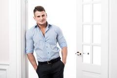 Portreta przypadkowy młody człowiek opiera przeciw ramie otwarte drzwi na lekkim tle uśmiechniętym i patrzeje kamera Obrazy Stock