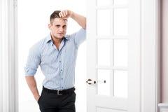 Portreta przypadkowy młody człowiek opiera przeciw ramie otwarte drzwi na lekkim tle uśmiechniętym i patrzeje kamera Obraz Stock