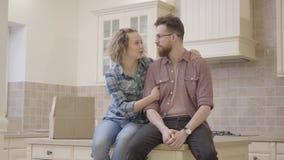 Portreta przystojny brodaty mężczyzna i śliczny kobiety obsiadanie na stole w kuchni w nowym mieszkaniu Rodzina dyskutuje plany zdjęcie wideo