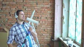 Portreta radosny i ekspresyjny męski budowniczy wyobraża sobie piosenkarza, podczas napraw, humor zdjęcie wideo