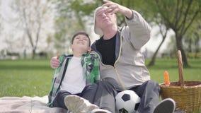 Portreta starego cz?owieka uroczy obsiadanie z jego wnukiem na koc w parku pokazuje niekt?re szczeg??y, wskazuj?cy w g?r?, zdjęcie wideo