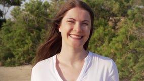 Portreta szczęśliwy ono uśmiecha się młodej kobiety pozycja w zieleń parku Wiatrowy dmuchanie jej włosy w zwolnionym tempie zbiory wideo