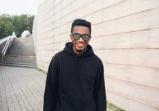 Portreta szczęśliwy uśmiechnięty afrykański mężczyzna w czarnym hoodie, okulary przeciwsłoneczni na miasto ulicie nad szarą ścian zdjęcie royalty free