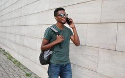 Portreta szczęśliwy uśmiechnięty afrykański mężczyzna wzywa smartphone odprowadzenie z plecakiem na miasto ulicie nad szarą ścian obrazy stock