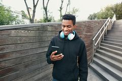 Portreta szczęśliwy uśmiechnięty afrykański mężczyzna z telefonem, hełmofony słucha muzyka jest ubranym czarnego hoodie, chodzi n obrazy stock