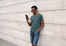 Portreta szczęśliwy uśmiechnięty afrykański mężczyzna z telefonem w zielonej koszulce, okulary przeciwsłoneczni na miasto ulicie  zdjęcia royalty free