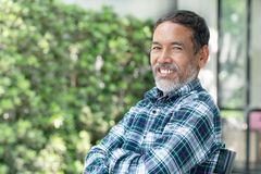 Portreta uśmiechnięty atrakcyjny dojrzały azjatykci mężczyzna przechodzić na emeryturę z elegancki krótki brody siedzieć plenerow fotografia stock