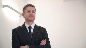 Portreta zadumany biznesowy mężczyzna w czarnym kostiumu główkowaniu z krzyżować rękami na klatce piersiowej zbiory wideo