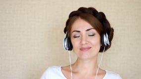 Portreta zbliżenia kobieta słucha muzykalna piosenka na lekkim tle w hełmofonach zdjęcie wideo