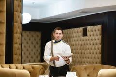 Portretchef-kok die een schotel bij het hotelrestaurant, presentatie voorstellen van de schotel door de chef-kok stock foto