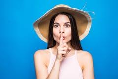 Portretclose-up die van vrouw strohoed dragen die vinger tonen bij lippen om geheim over blauwe achtergrond geïsoleerd te houden royalty-vrije stock fotografie