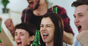 Portretclose-up van charismatische en knappe vrienden multi etnisch terwijl het letten van op een voetbalwedstrijd die zij hebben stock video