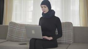 Portretjongelui die succesvol zeker meisje in achterkleren en mooi hoofddeksel glimlachen die met haar laptop werken stock videobeelden