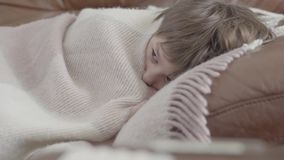Portretjongen die die op de bank liggen met een deken thuis wordt behandeld Het leuke kind rust De jongen is ziek, voelt hij koud stock videobeelden