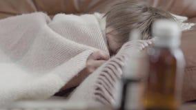 Portretjongen die die op de bank liggen met een deken thuis wordt behandeld Het leuke kind rust r geneeskunde stock video