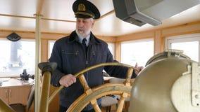 Portretkapitein van het stuurwiel van de schipholding op kapiteinsbrug Gebaard zeeman het draaien roer terwijl het varen stock footage