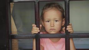 Portretmeisje die uit het venster, van buiten kijken die in langzame motie wordt geschoten stock footage