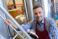 Portretmens die trap in distilleerderij beklimmen stock foto's