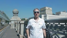 Portretmens op middelbare leeftijd, heldere zonnige dag, bevindt hij zich brug in zonnige glazen stock footage