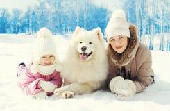 Portretmoeder en kind met witte Samoyed-hond die samen op sneeuw in de winter liggen Royalty-vrije Stock Foto