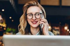 Portretonderneemster die in glazen in koffie voor laptop zitten, die op telefoon spreken Het meisje blogger communiceert telefoni stock foto