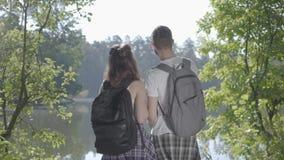 Portretpaar die zich op riverbank in het bos met rugzakken bevinden die weg richten De jonge man en vrouwen wandeling stock videobeelden