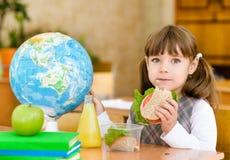 Portretschoolmeisje die camera bekijken terwijl het hebben van lunch tijdens Stock Foto's