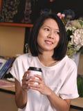 Portretten die van Aziatische vrouw een kop van koffie houden door twee handen die aan haar linkerhand in comfortabele koffiewink royalty-vrije stock afbeelding