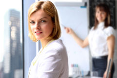 Portretten van bedrijfsvrouw dichtbij venster Presentatie op een achtergrond stock foto