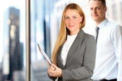 Portretten van bedrijfsvrouw en de mens die zich dichtbij venster bevinden Royalty-vrije Stock Afbeelding
