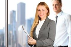 Portretten van bedrijfsvrouw en de mens die zich dichtbij venster bevinden Stock Foto's