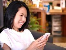 Portretten van het Aziatische vrouw kijken aan haar witte smartphone royalty-vrije stock foto