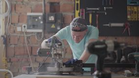 Portretvaardigheid craftman in beschermingsglazen die een houten raad met een kleine cirkelzaag op de lijst in snijden stock footage