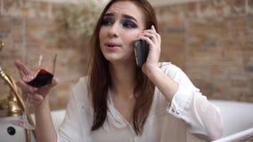 Portretvrouw die door celtelefoon spreken die gebaren met wijn dicht omhoog glas maken in badkamers stock footage