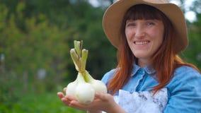 Portretvrouw die een bos die van witte uien houden, zich dichtbij de tuin bevinden stock footage