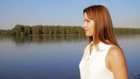 Portretvrouw die zich op de rivierkust bevinden portret van glimlachende vrouw op de bank van de rivier Sluit omhoog stock video