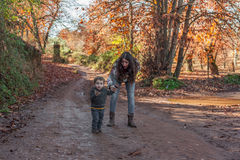 Portretvrouw en leuke babyjongen die van een aardgang genieten De herfst stock fotografie