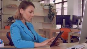 Portretvrouw met gadget op het werk stock videobeelden