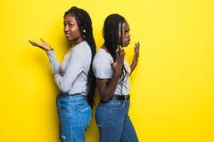 Portriat 2 отрицательных африканских женщин стоя с оружиями пересеченными после ссоры изолированной над желтой предпосылкой стоковые фото