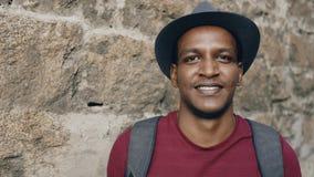 Portriat av den lyckliga afrikanska turist- manfotvandraren som ler och ser in i kamera Ung grabbresande för blandat lopp in royaltyfri fotografi