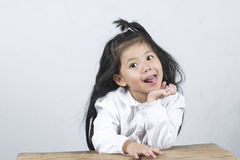 Portriat  Cheerful  of a Funny Cute Asian Girl. Portriat  Cheerful  of a Funny Cute Asian Girl on a wooden table copy space on white background Stock Photos