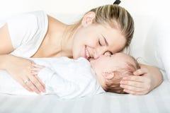 Portriat de jeune mère heureuse avec les yeux fermés se trouvant sur le lit à côté de ses 3 mois de bébé garçon Photographie stock libre de droits