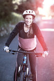 Portriat del motorista femenino con la bici de montaña en campo Imagen de archivo