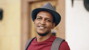 Portriat del viaggiatore con zaino e sacco a pelo turistico africano felice dell'uomo che sorride e che esamina macchina fotograf Immagine Stock Libera da Diritti