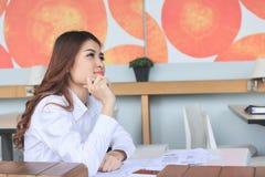 Portriat der attraktiven jungen asiatischen Geschäftsfrau, die über etwas denkt und träumt Lizenzfreie Stockfotos