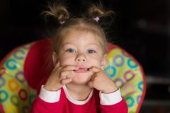 Portriat of little girl playing the ape looking at camera stock image